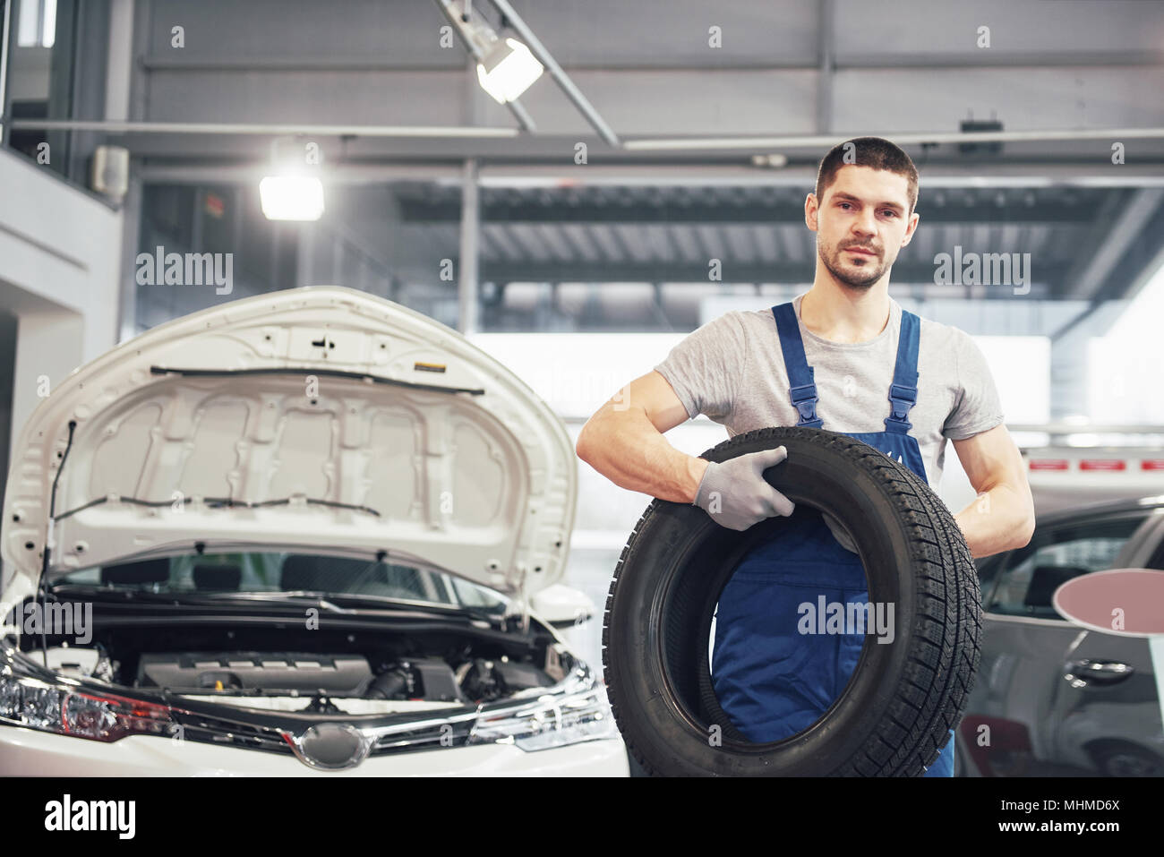 Mechanic holding a tire tire at the repair garage. replacement of winter and summer tires Stock Photo