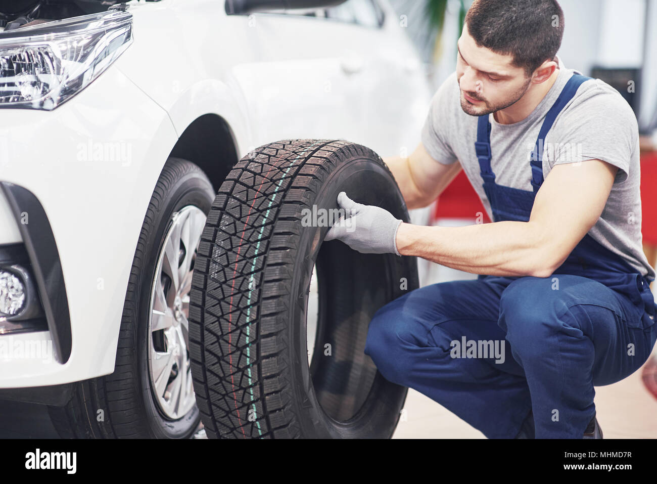 Mechanic holding a tire tire at the repair garage. replacement of winter and summer tires - Stock Image