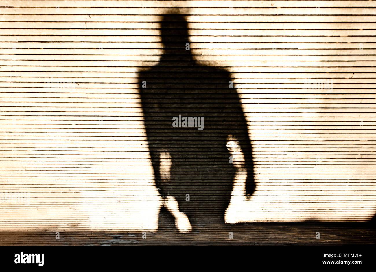 Blurry shadow silhouette of a man walking on patterned sidewalk - Stock Image