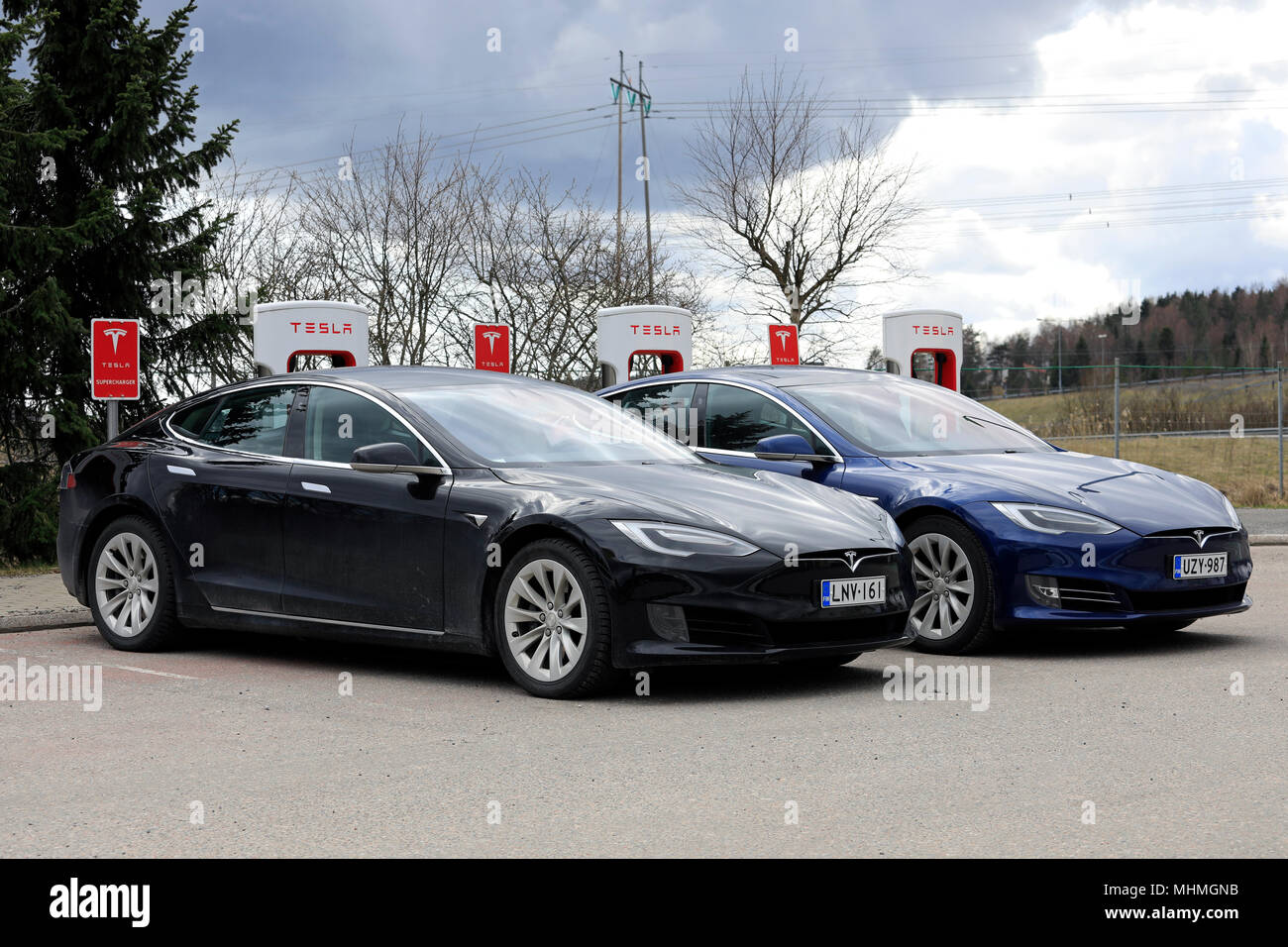 Two Tesla Model S electric cars of the updated or facelift exterior design are charging battery at Supercharger station on a day of spring in Paimio,  Stock Photo