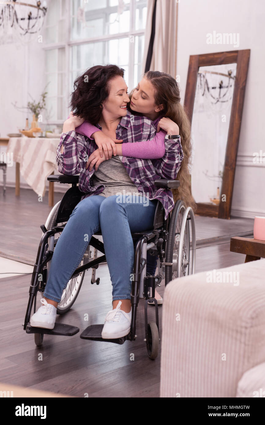 Pretty girl adoring disabled woman - Stock Image