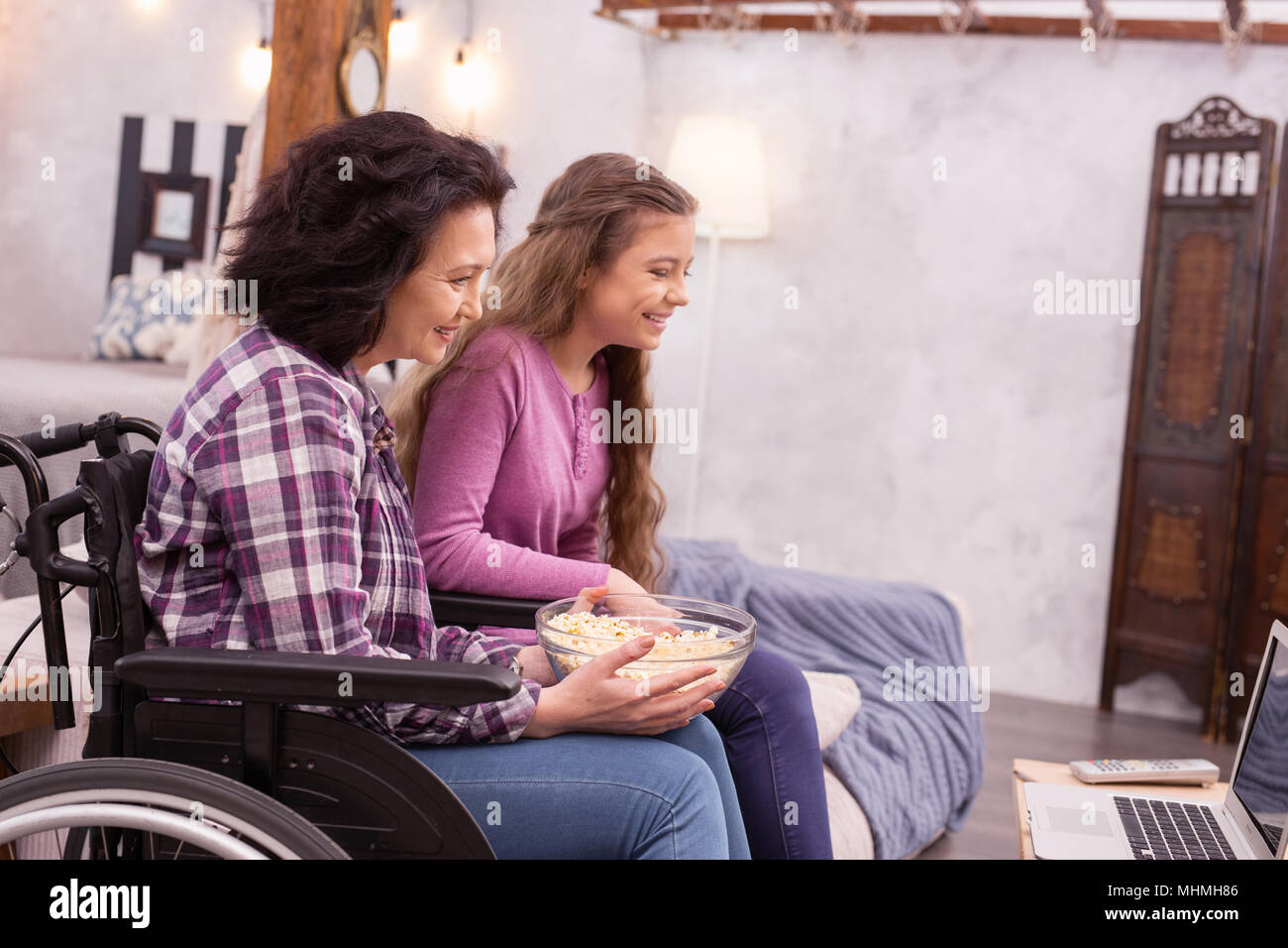 Positive incapacitated woman and girl seeing movie - Stock Image