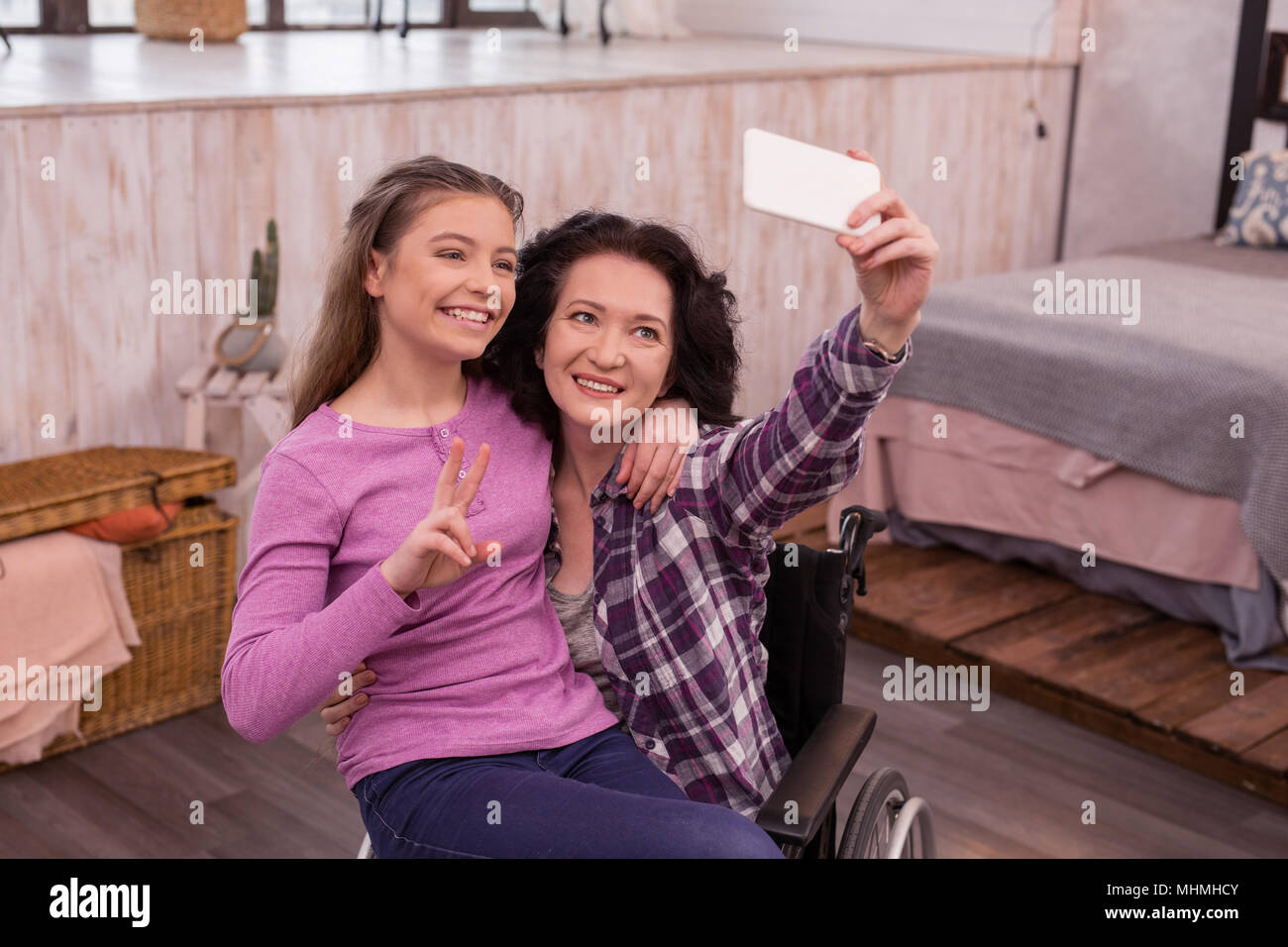 Joyful crippled woman and girl taking selfie - Stock Image