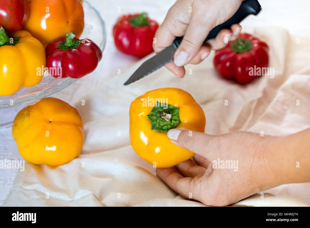 Woman hand with knife seeding tomato peppers. - Stock Image