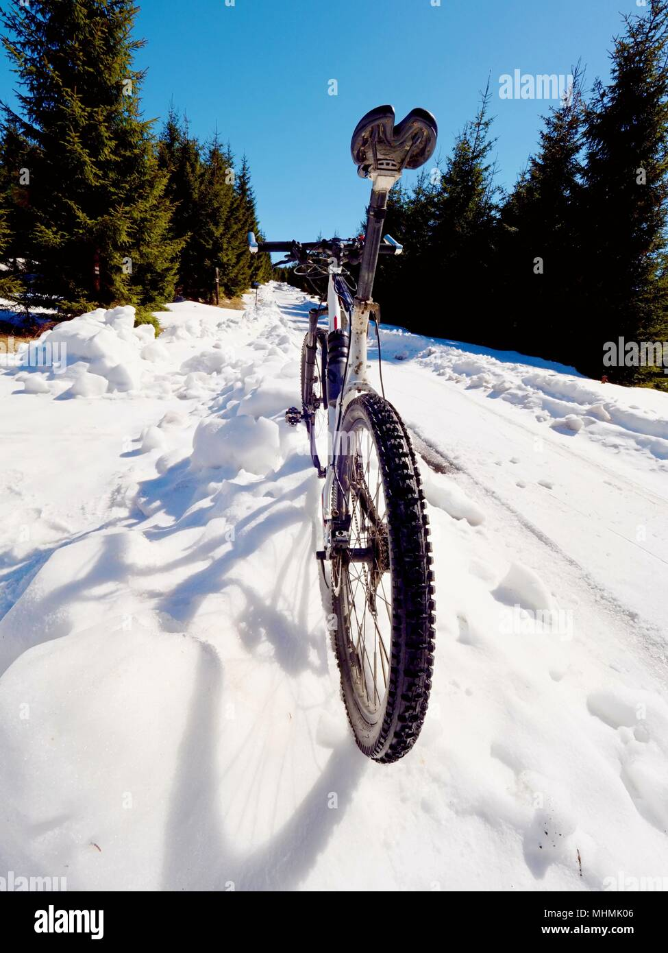Mountain bike standing in frozen snow against blue sky. Hidden  asphalt road under sow cover. Extreme adrenalin sports - Stock Image
