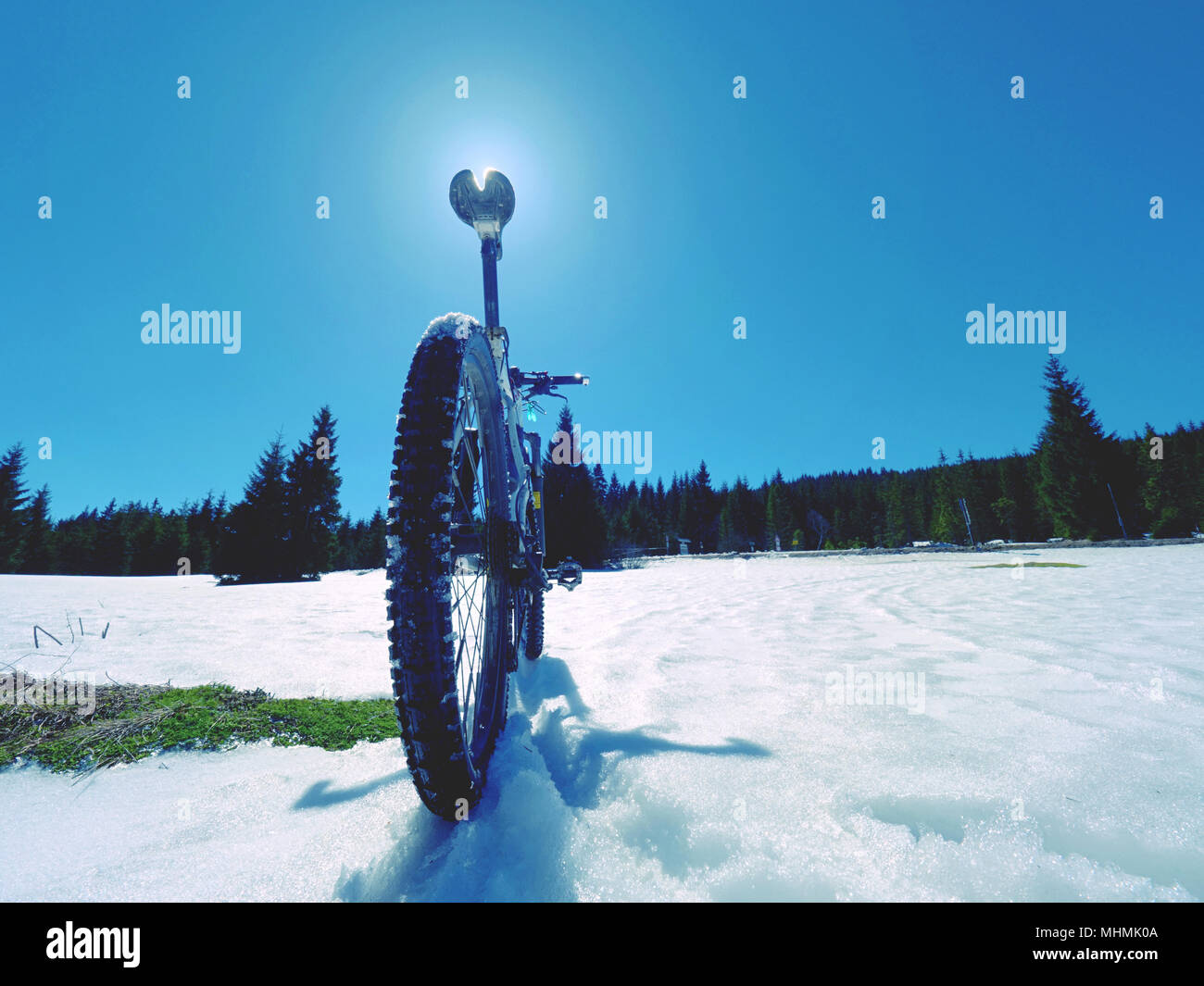 Cycling on large tyres in fresh snow. Biker goes by bike on the snowy road in the mountains. Picture taken in HDR mode. Stock Photo
