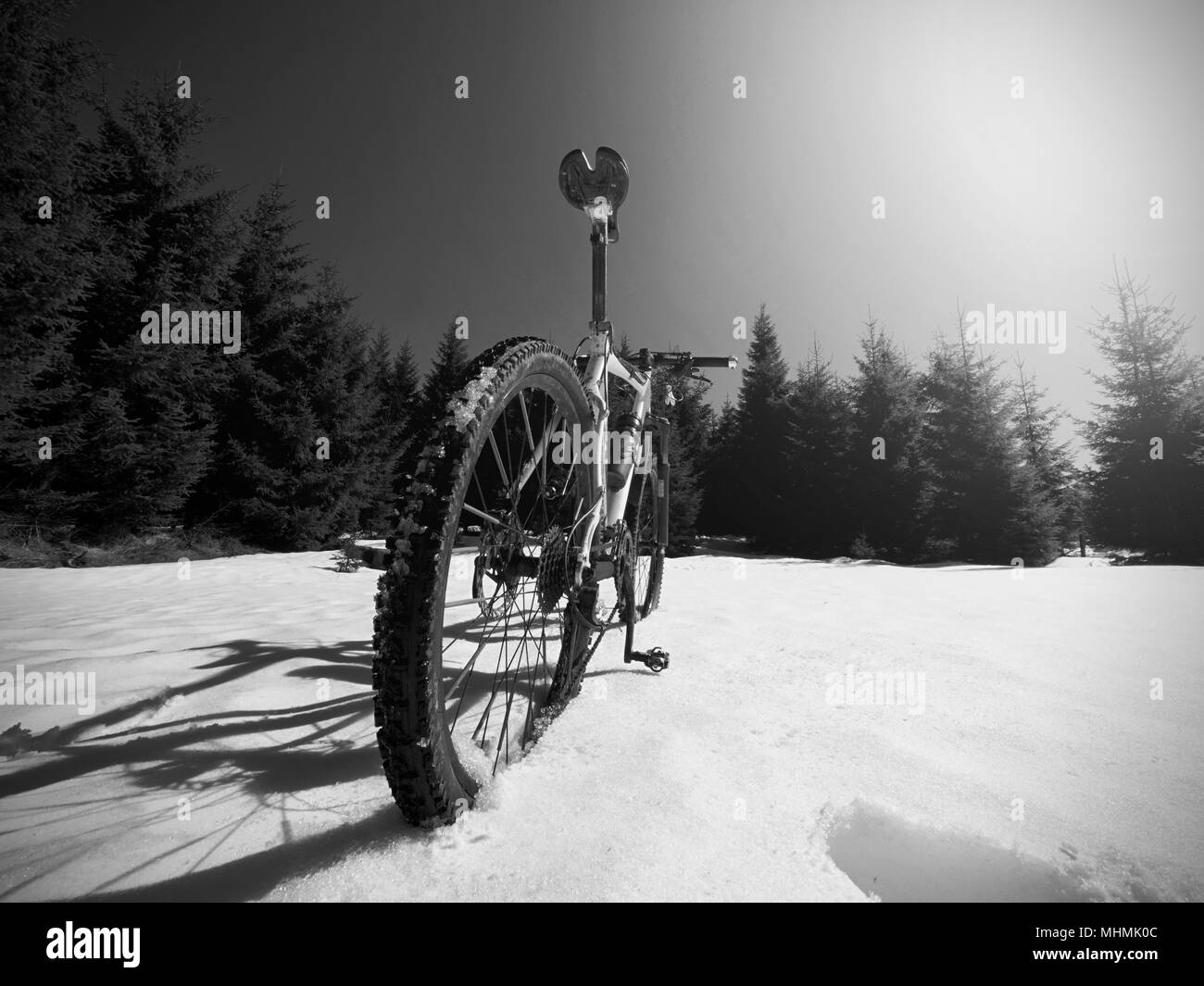 Cycling in winter snowy mountains on large tire wheels mountain bike. Sunny winter day. - Stock Image