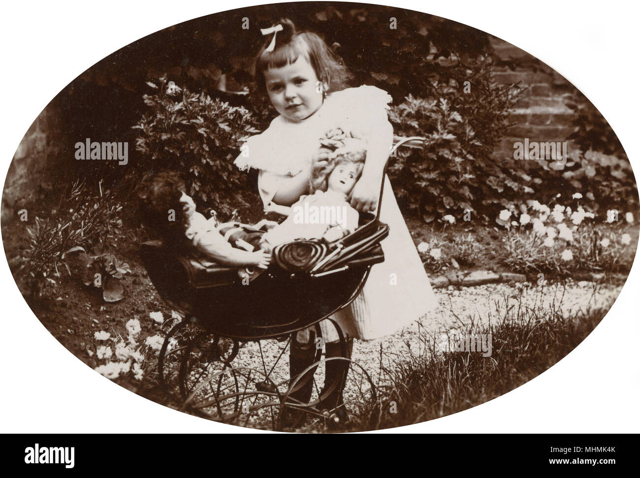 A little girl of Neufchatel, France, wheels her two dolls in their pram.       Date: circa 1920 ? - Stock Image