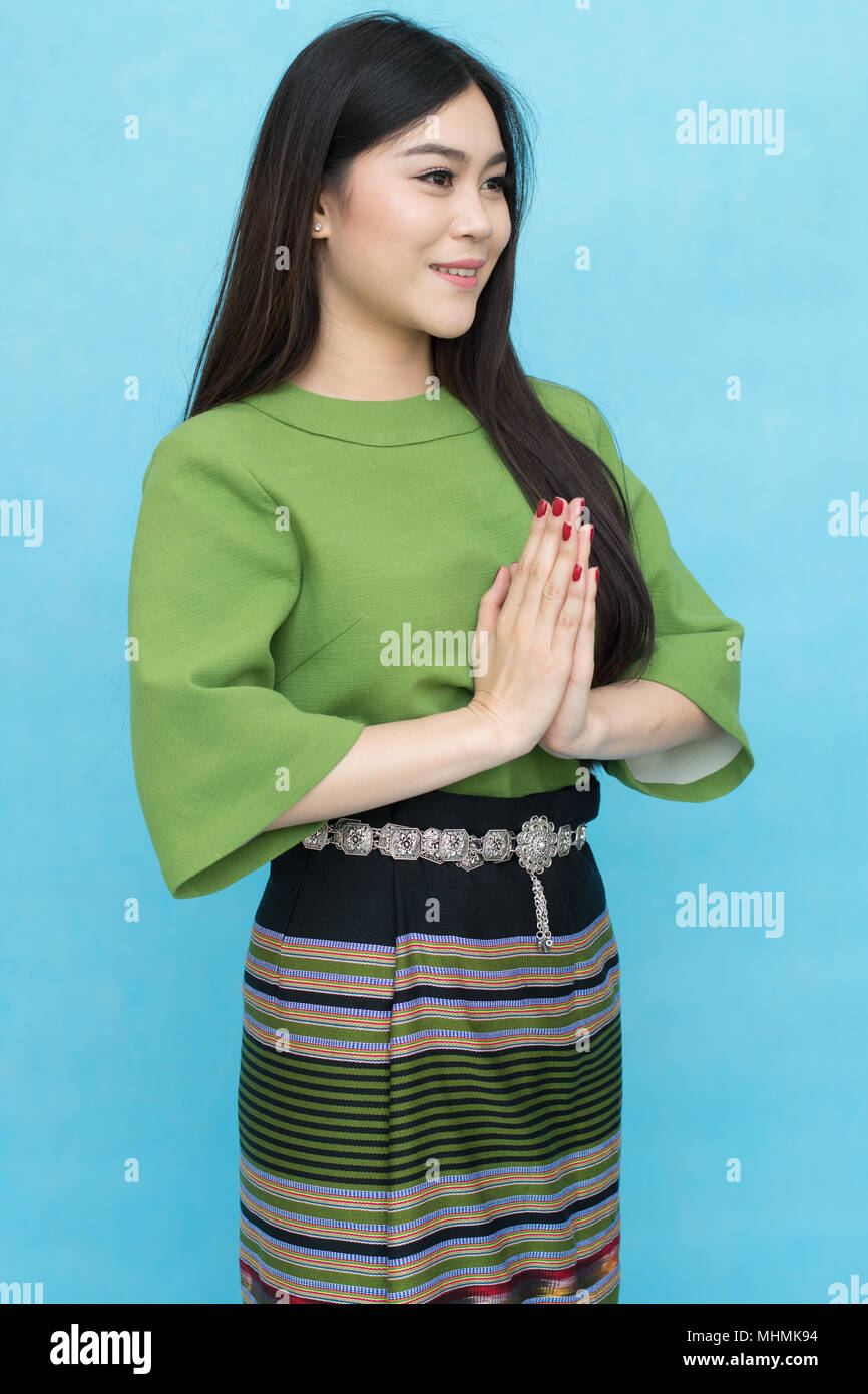 68c33e8c6 Portrait of asian young girl in traditional thai dress praying isolated on  blue sky background. Wai Sawatdee mean welcome to Thailand. Amazing Travel