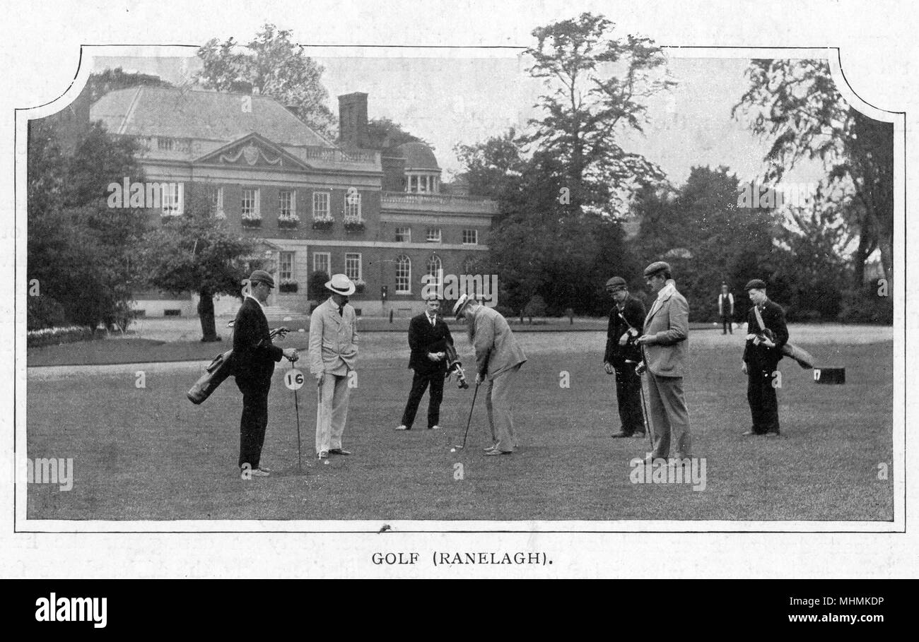 Elegantly dressed golfers watch a partner putt out on the sixteenth green at Ranelagh Golf Club, England.      Date: 1900 - Stock Image