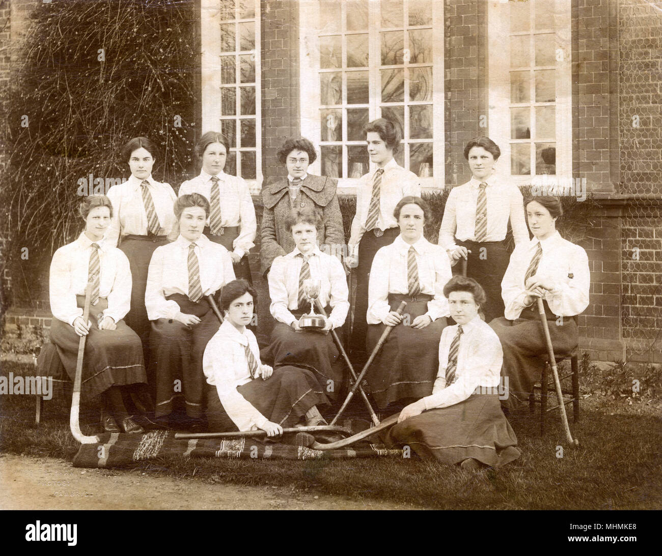 A photograph of the Newnham College, Cambridge ladies hockey team; the captain sits in the centre with a trophy.       Date: 1904 - Stock Image