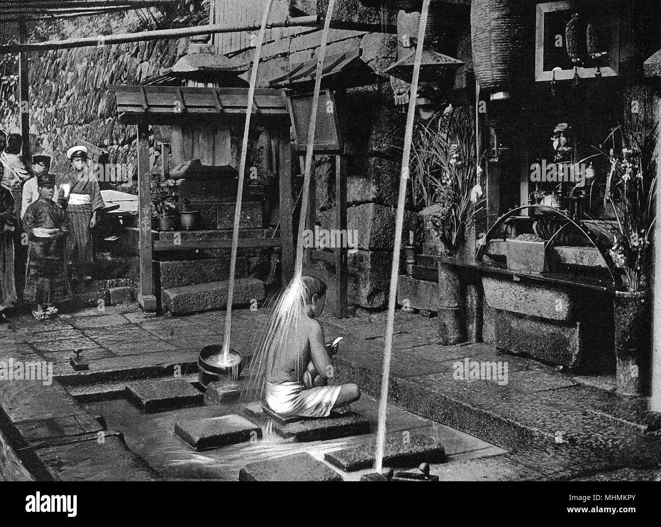 A Japanese liar is purified; he sits underneath a stream of cold water which beats down onto his back.       Date: 1904 - Stock Image