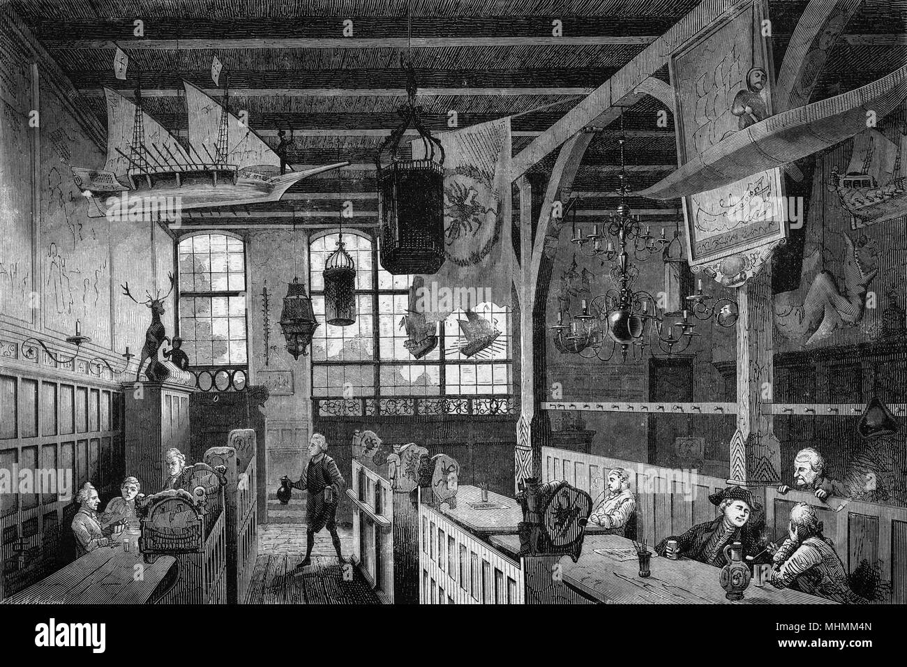 Men drink and smoke in a bierkeller in Lubeck, Germany, with an interesting range of ephemera hanging from the ceiling.      Date: 1870 - Stock Image
