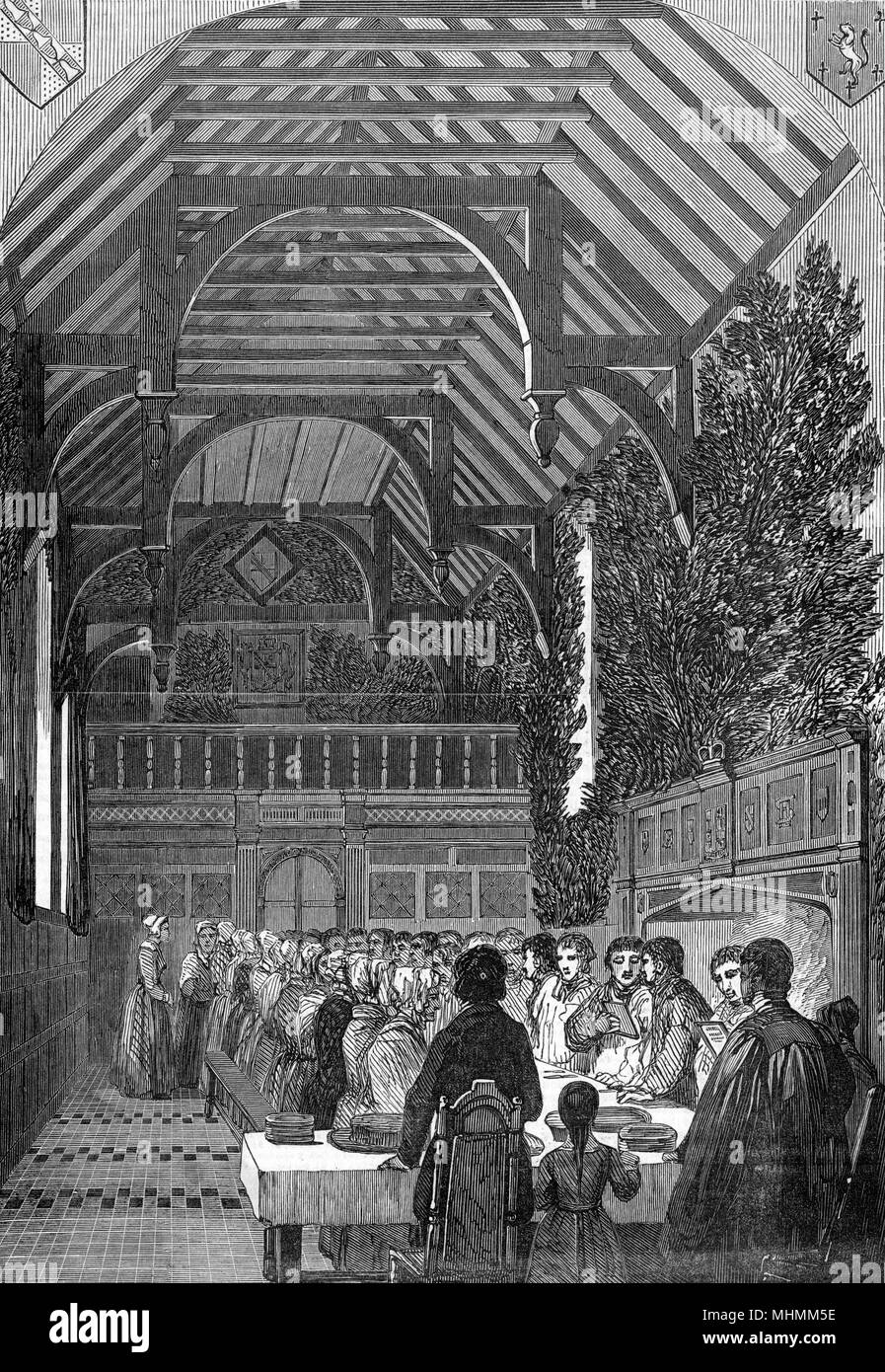 The residents of Sackville College, East Grinstead, Surrey, celebrate Palm Sunday in the timbered and vaulted hall of their almshouse.      Date: 1850 - Stock Image