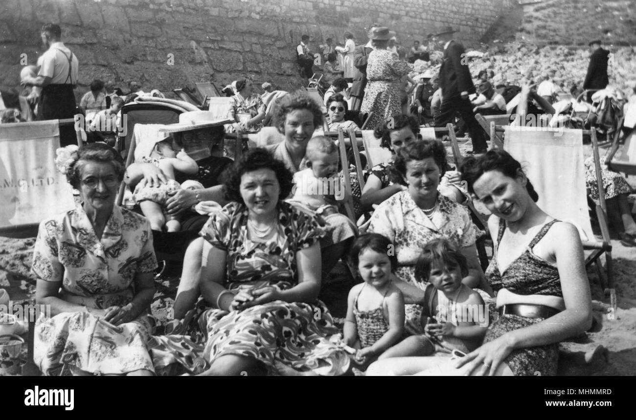 A family pose for an informal photograph on the beach at an unidentified seaside resort.  Assorted relatives in varying states of dress from a lady in a bikini at the front to a grandmother in dress and sunhat holding a baby in a deckchair in the background.  The beach is looking particularly busy.       Date: c.1952 - Stock Image