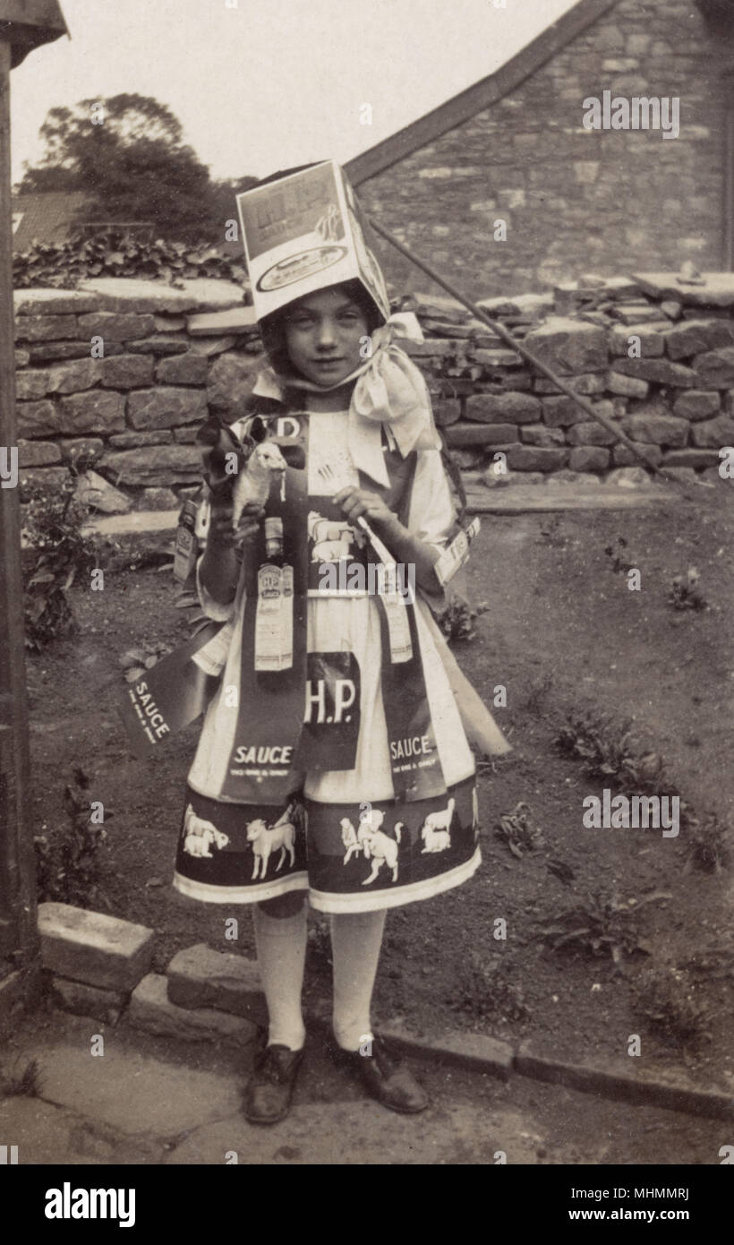 A young girl posing in her HP sauce themed fancy dress costume.       Date: c.1920 - Stock Image