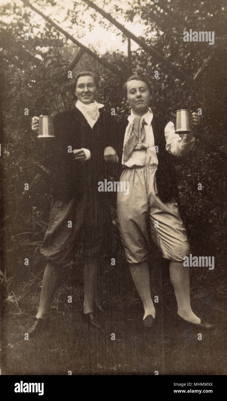 Two women in fancy dress costumes comprising of knickerbockers, shirts and waistcoats, raise a tankard of beer each - presumably they're meant to be some kind of 17th century roisterers?     Date: c.1928 - Stock Image
