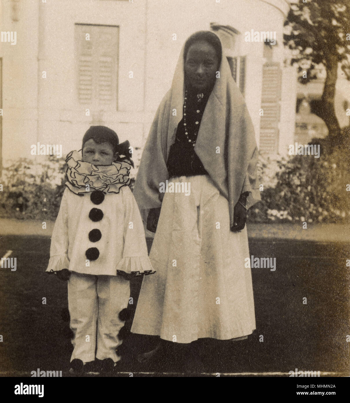 A little boy dressed up in a clown fancy dress costume for a party.  He appears to be accompanied by his nurse, or ayah - the photograph looks to be taken on the Indian sub-continent.       Date: 1920s - Stock Image