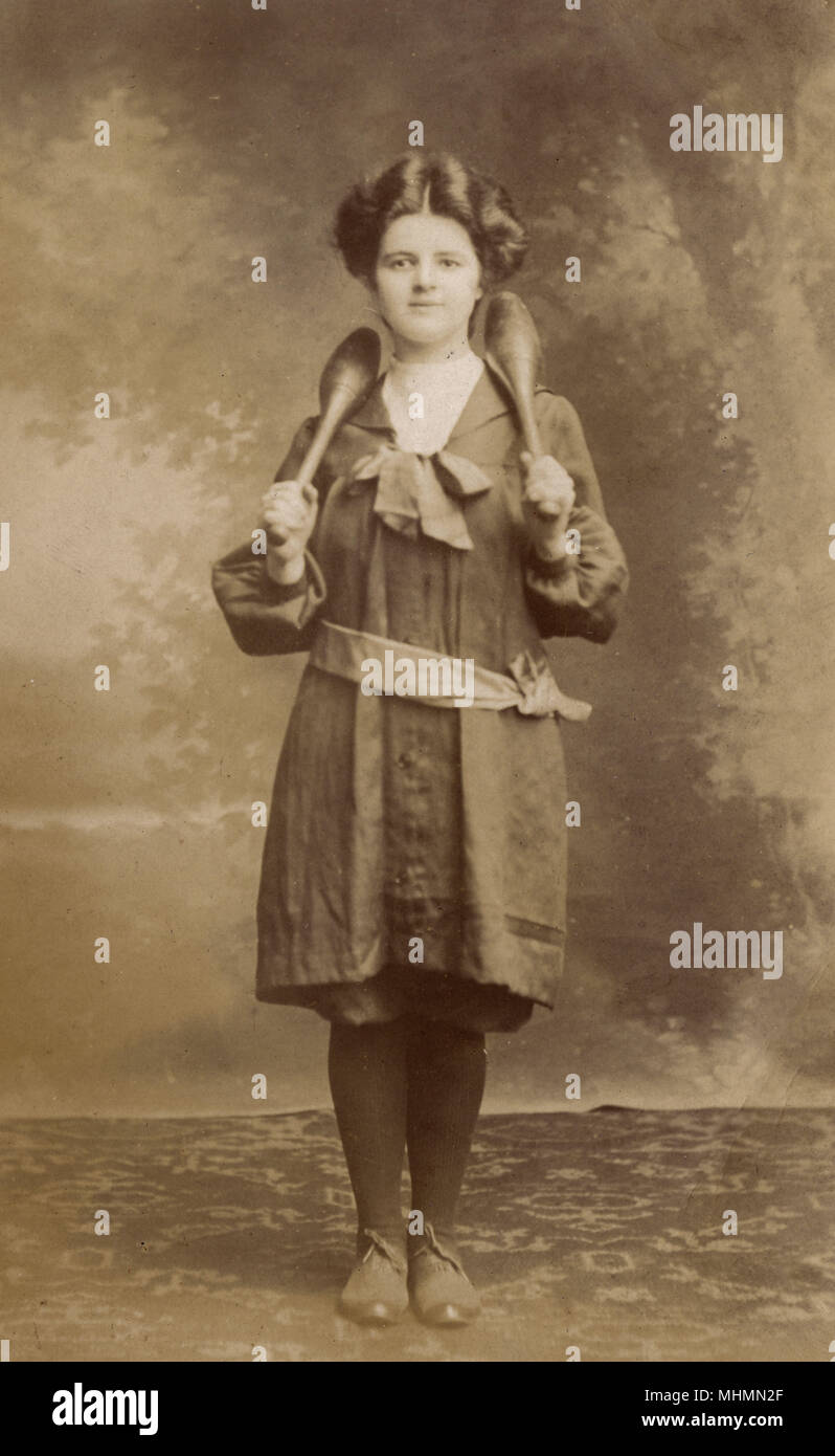 A young girl in the Edwardian era posing in her 'sports kit' with some wooden clubs, frequently used for exercising with at this time.       Date: c.1910 - Stock Image