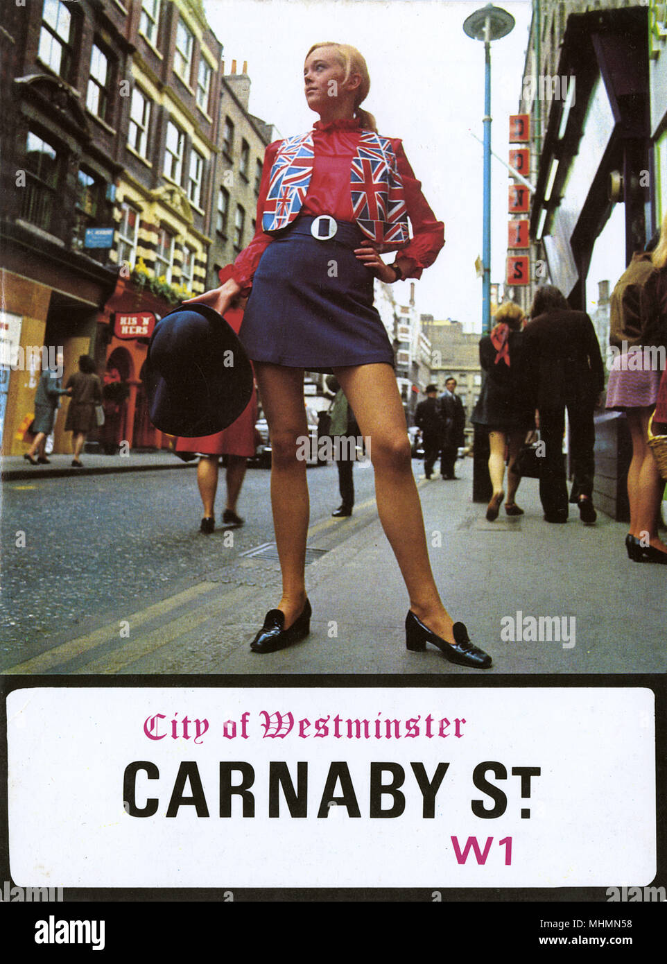 Front cover of a promotional booklet about fashion epicentre of the 1960s, Carnaby Street, London.  A model poses in front of the street's various boutiques wearing a Union Jack waistcoat and mini skirt.     Date: 1966 - Stock Image
