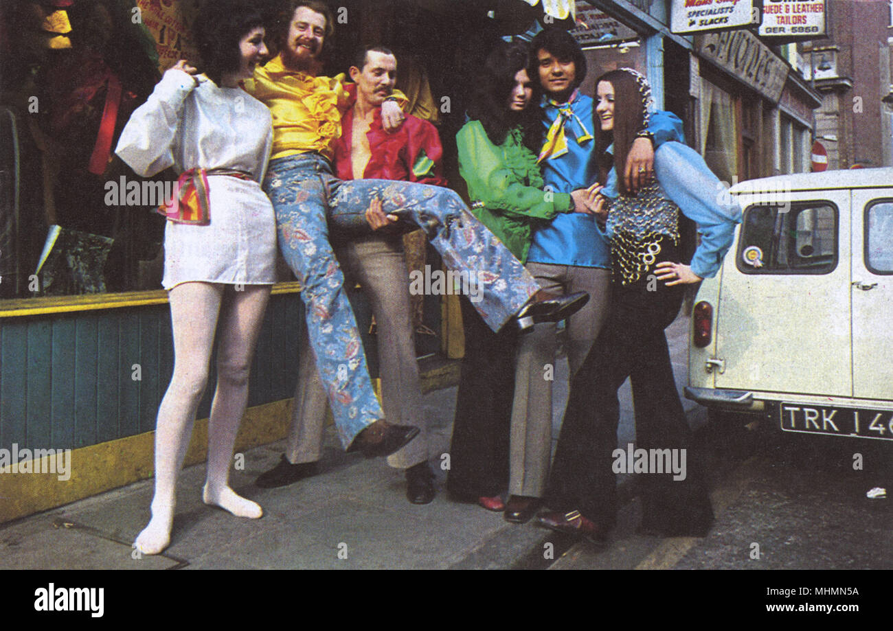 A group of groovy people wearing flamboyant fashions of the 1960s in Carnaby Street, London.       Date: 1966 - Stock Image