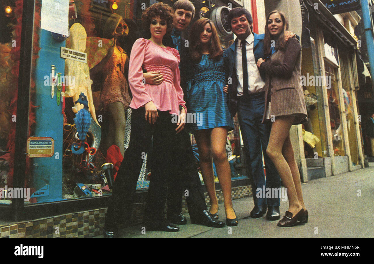 A group of groovy people posed outside a boutique in Carnaby Street, London, including radio DJ Tony Blackburn.      Date: 1967 - Stock Image