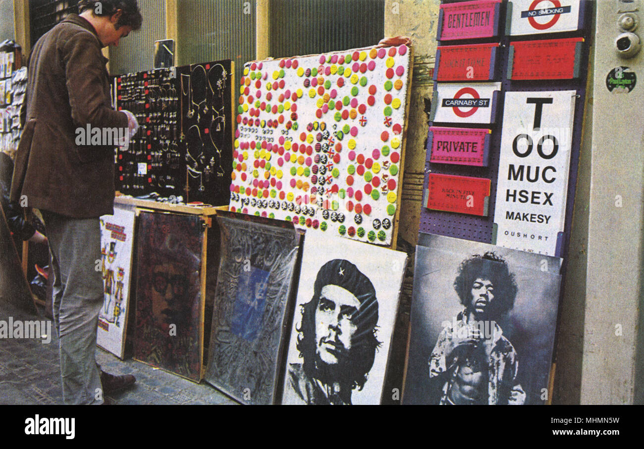 Badges, jewellery, London street signs and posters of Bob Dylan, Che Guevara and Jimi Hendrix for sale on Carnaby Street, beating heart of swinging sixties London.      Date: 1967 - Stock Image