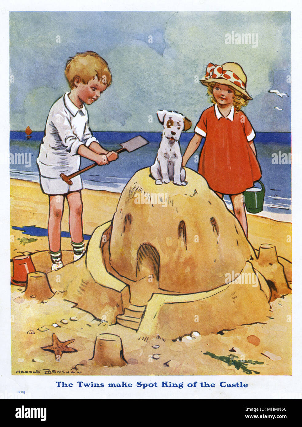 Two children build an impressive sandcastle atop which their little dog decides to sit.       Date: c.1920 - Stock Image