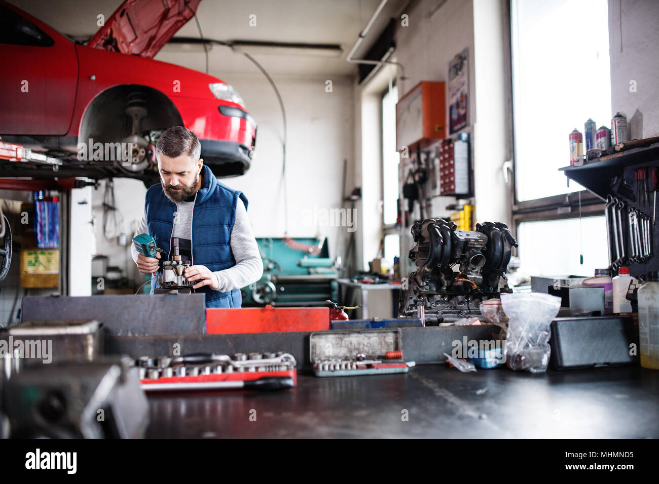 Man mechanic repairing a car in a garage. - Stock Image