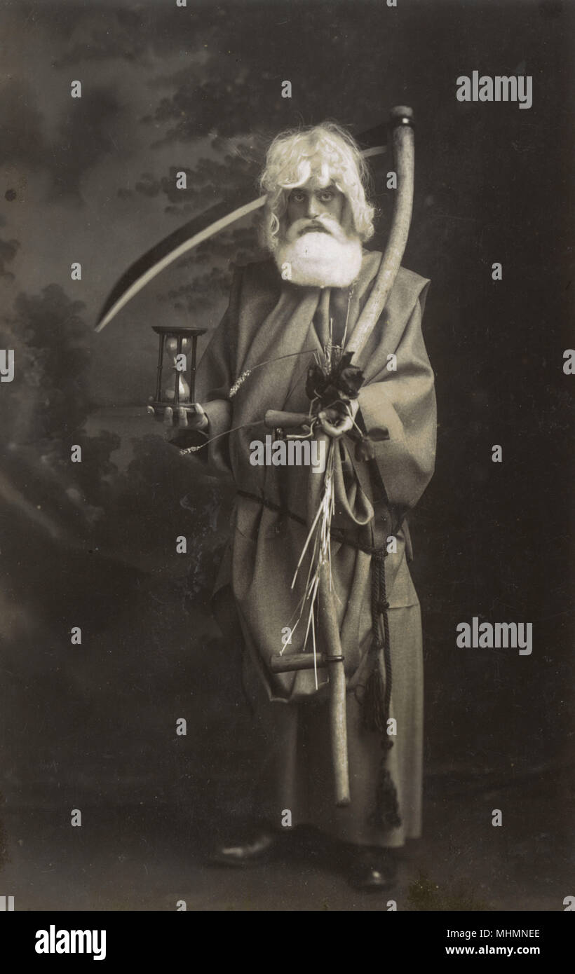 A man dressed up as Old Father Time with obligatory scythe and hour glass.       Date: c.1920 - Stock Image