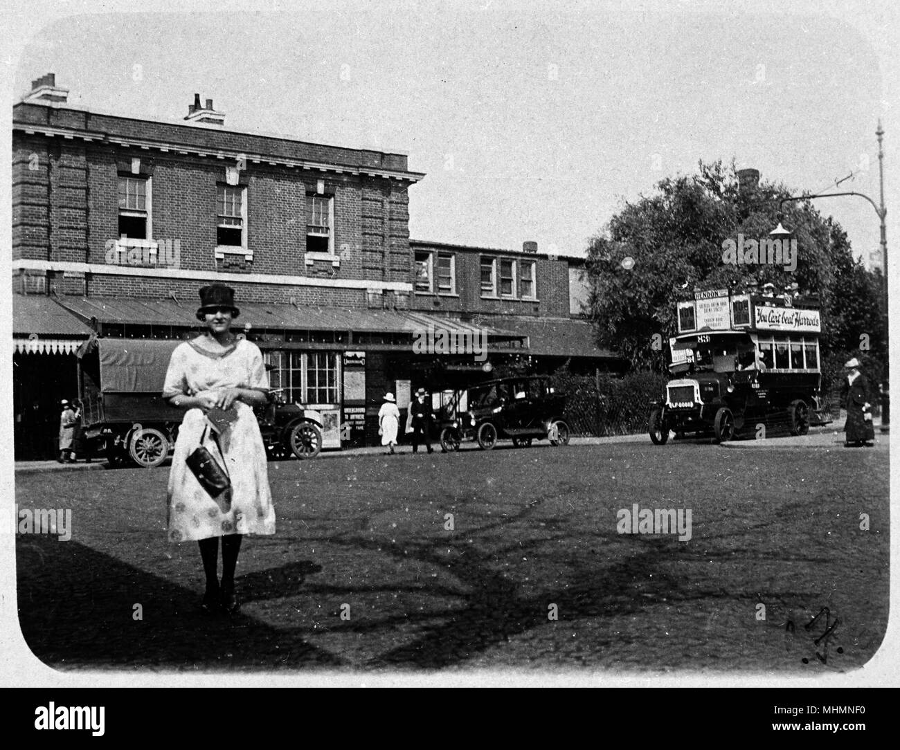 Woman outside Golders Green underground station, London. The bus, destination Hendon, carries an advertisement: You Can't Beat Harrods.      Date: 1921 - Stock Image