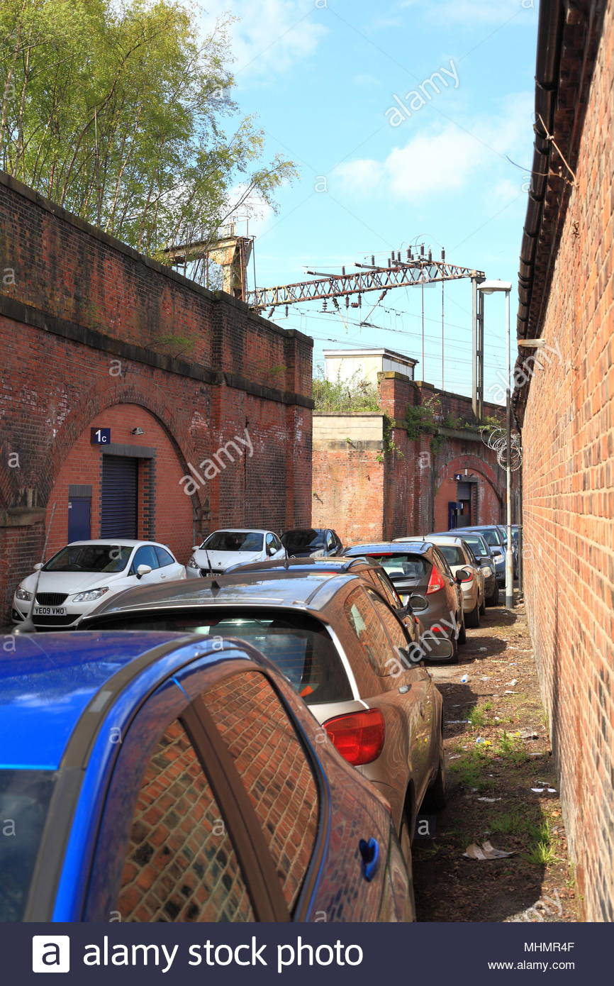 Cars Parked On The Narrow Back Streets Of Ardwick Greater Manchester At The Ardwick Railway Station Platform Stock Photo