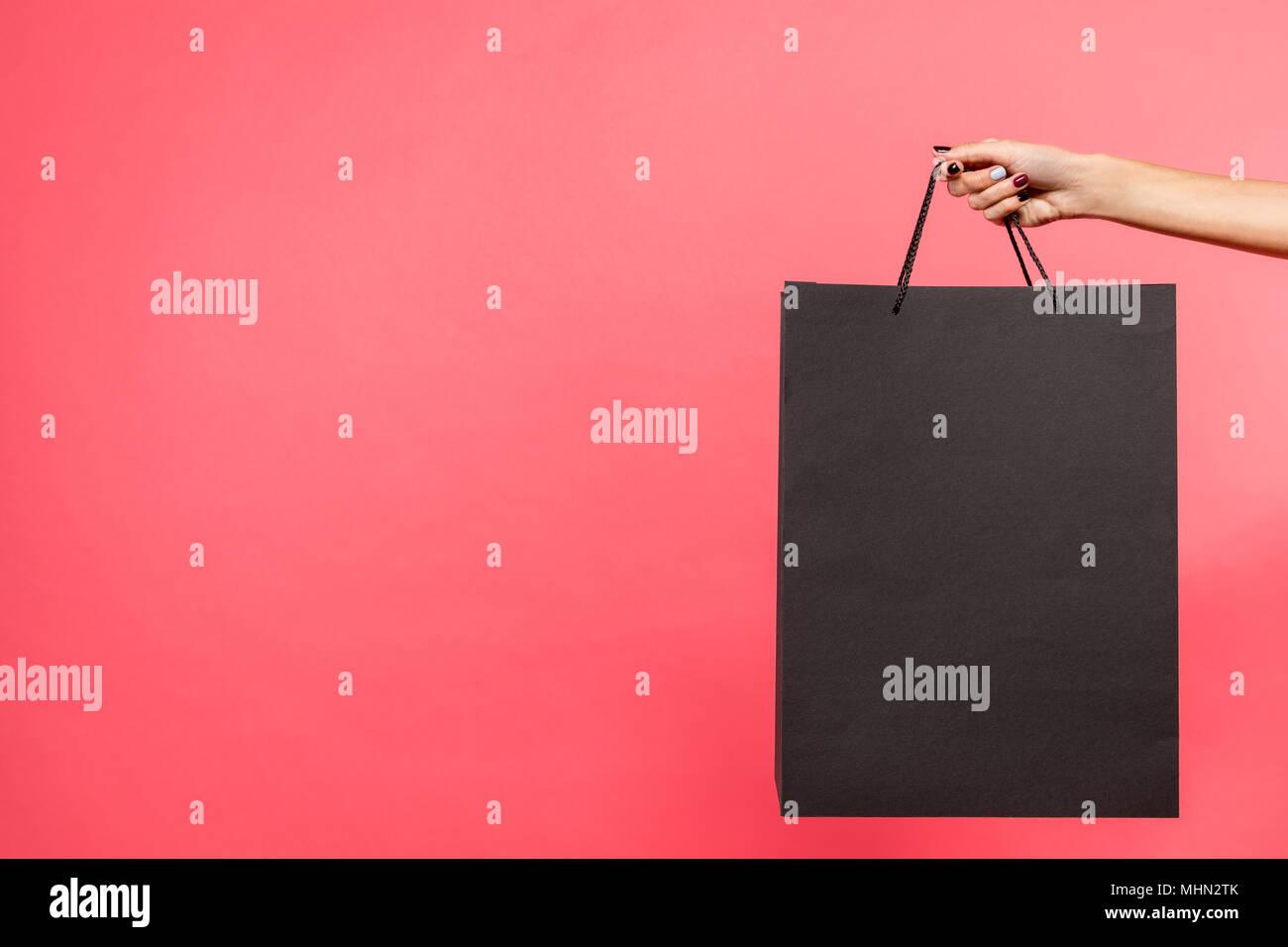 woman holding black shopping bag - Stock Image