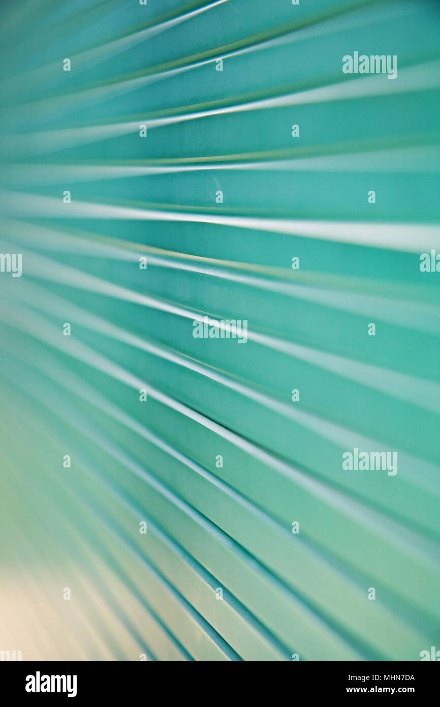 Macro shot of a stack of green glass panels with converging lines and shallow depth of field. - Stock Image
