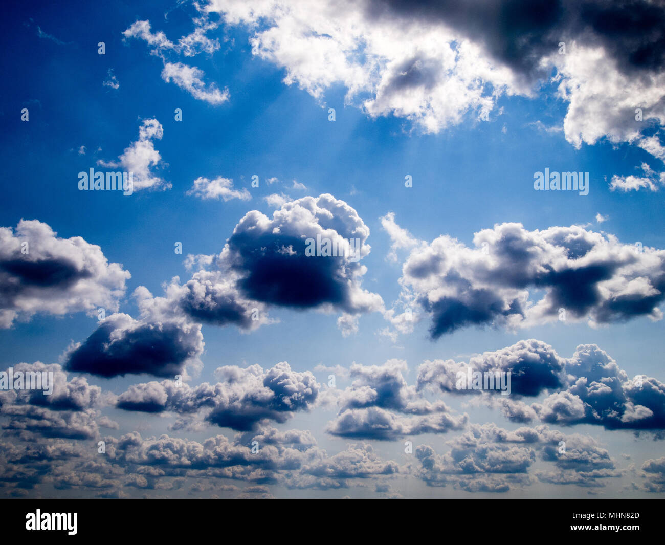 Blue sky with white fluffy clouds - Stock Image
