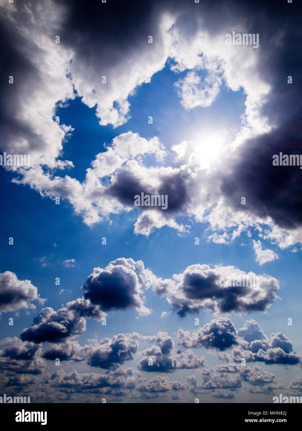 Blue sky with white fluffy clouds and sun - Stock Image