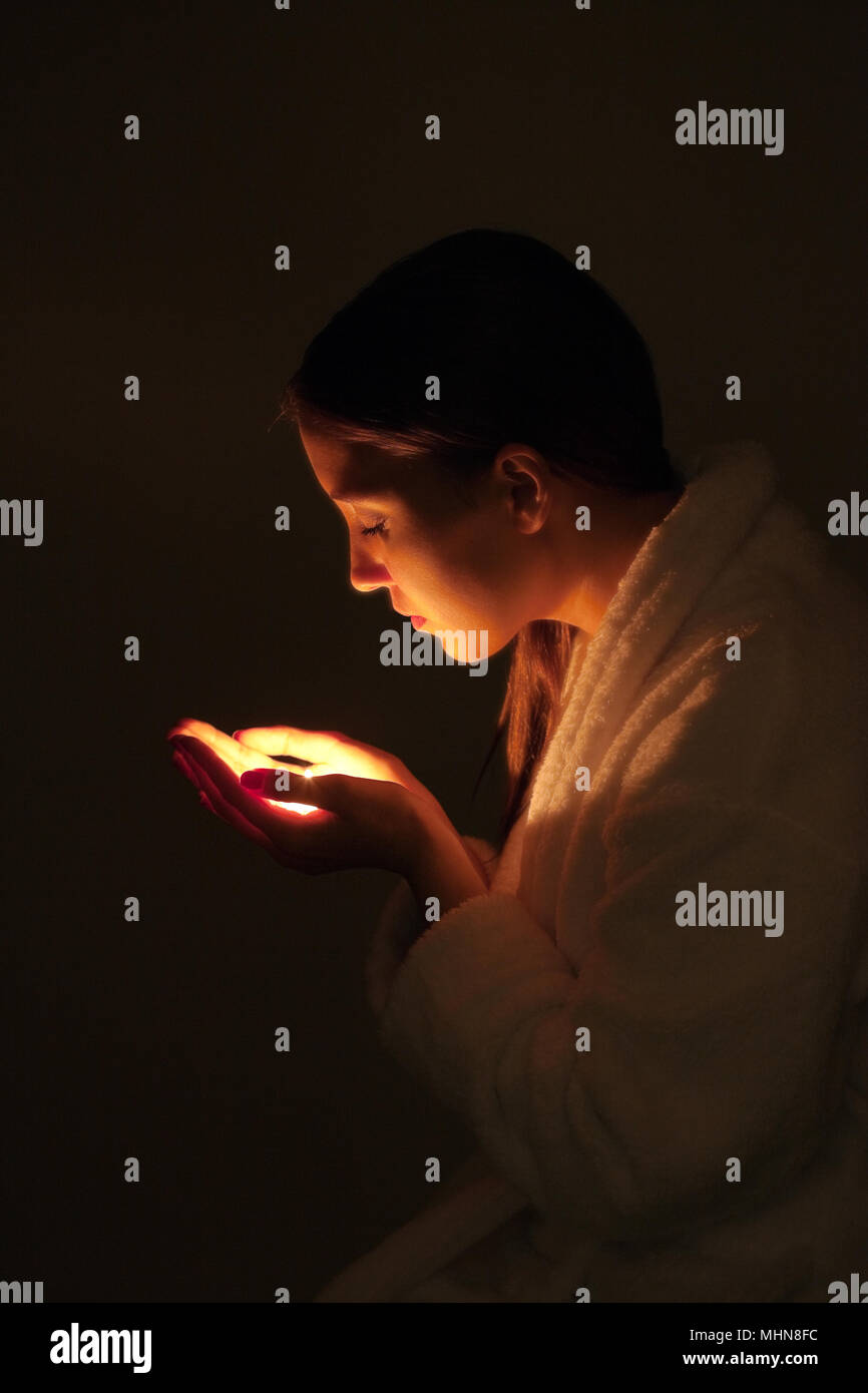 Young woman in a bathrobe holding a candle - Stock Image