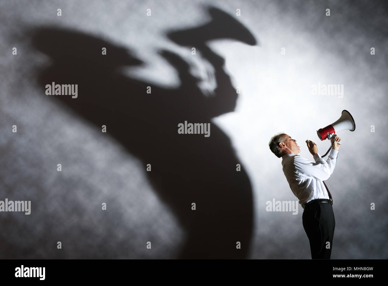 Man with megaphone and enormous shadow - Stock Image