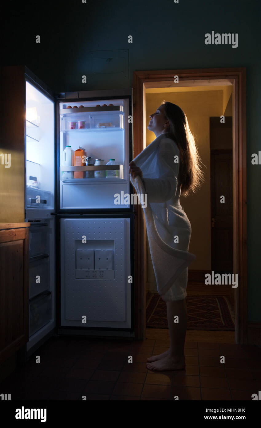 Woman opening her bathrobe in front of the fridge to cool off - Stock Image