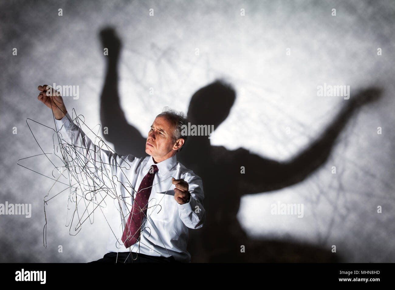Man untangling a mass of coat hangers - Stock Image