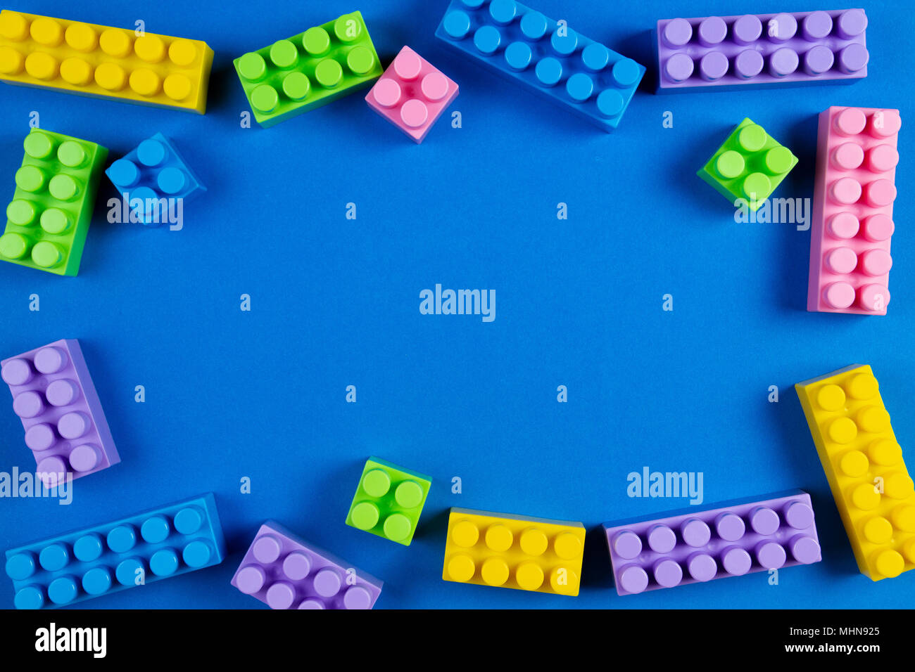 Colorful Plastic Construction Blocks On Blue Background As Kids Toys