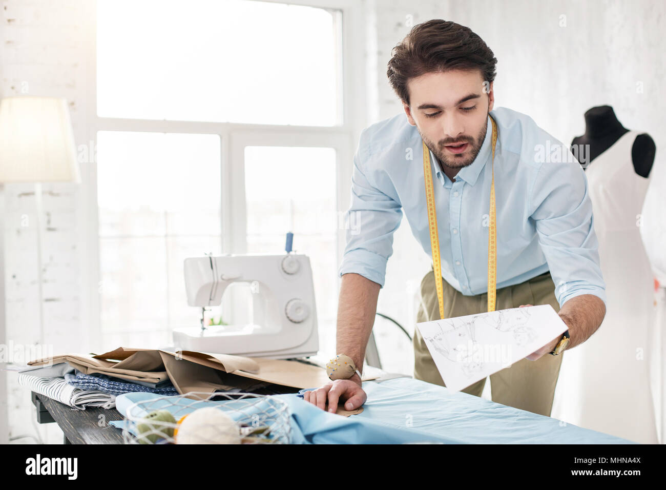 Serious professional tailor holding his sketches - Stock Image