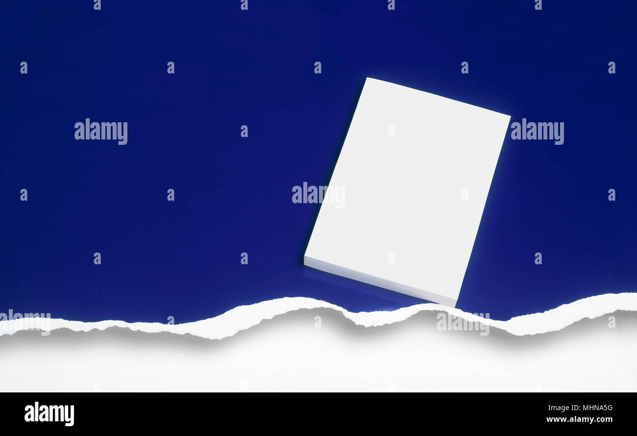 Graphic resource. Blank cover book against a ripped blue background. Clipping path on cover book. - Stock Image
