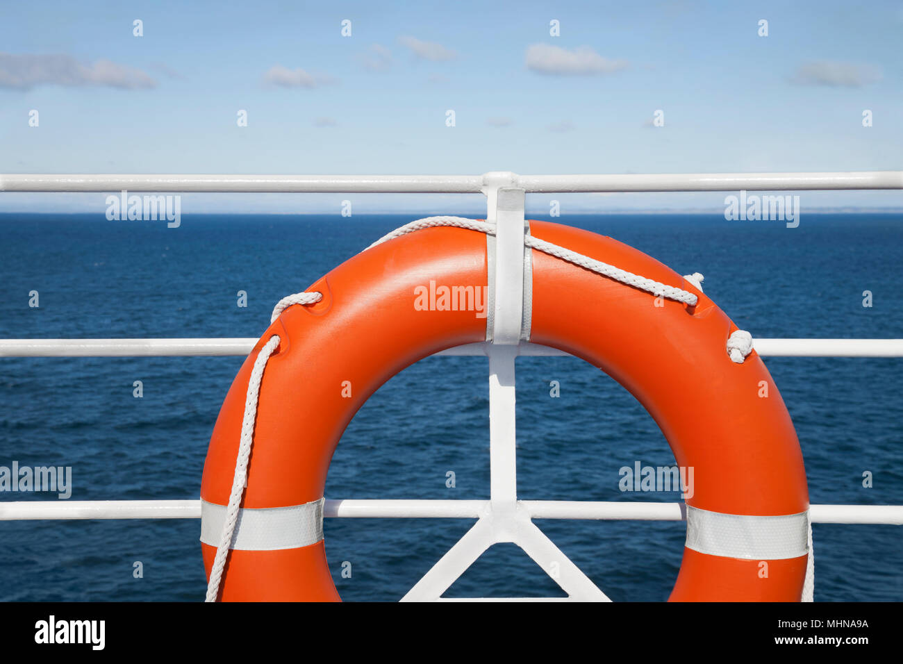 Lifebuoy and hand railing deck at cruise ship against seascape in a sunny day. Travel concept - Stock Image