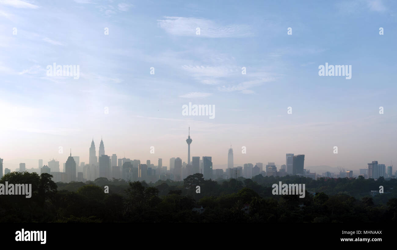 panorama view of beautiful kuala lumpur cityscape skyline in the hazy or foggy morning enviroment and buildings in silhouette with copy space Stock Photo