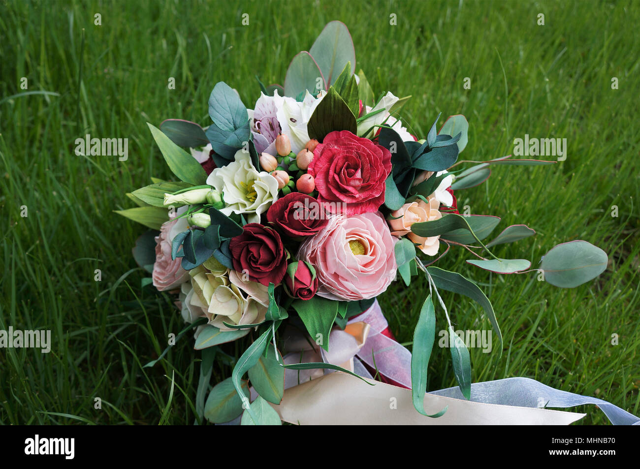 Artificial flowers made from sponge rubber. Bouquet for the bride. Foam-iran. Beautiful colorful wedding bouquet. Handmade flower fabric foamiran on t - Stock Image