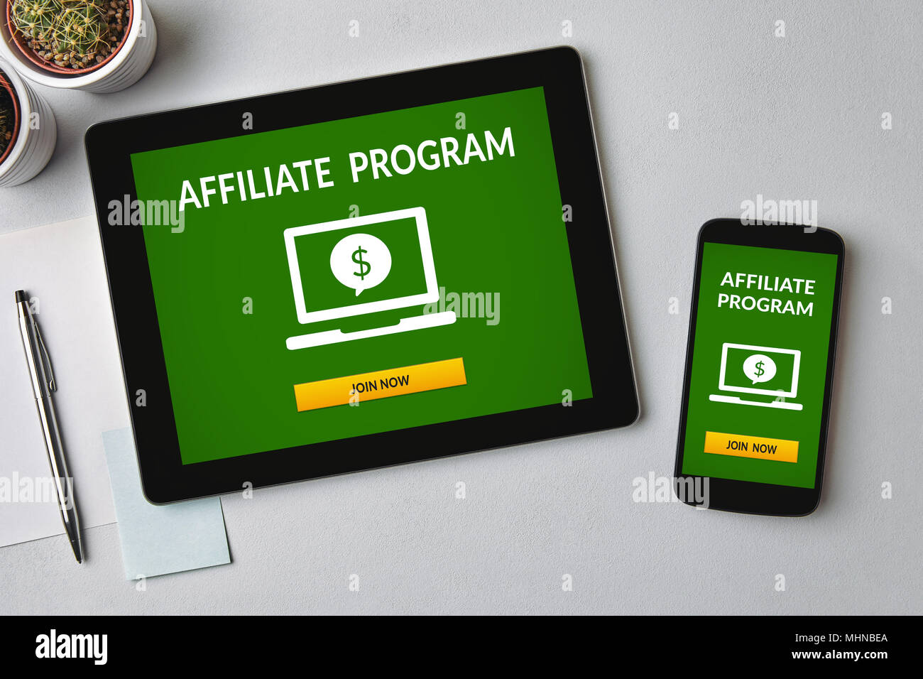 Affiliate program concept on tablet and smartphone screen over gray table. All screen content is designed by me. Flat lay - Stock Image