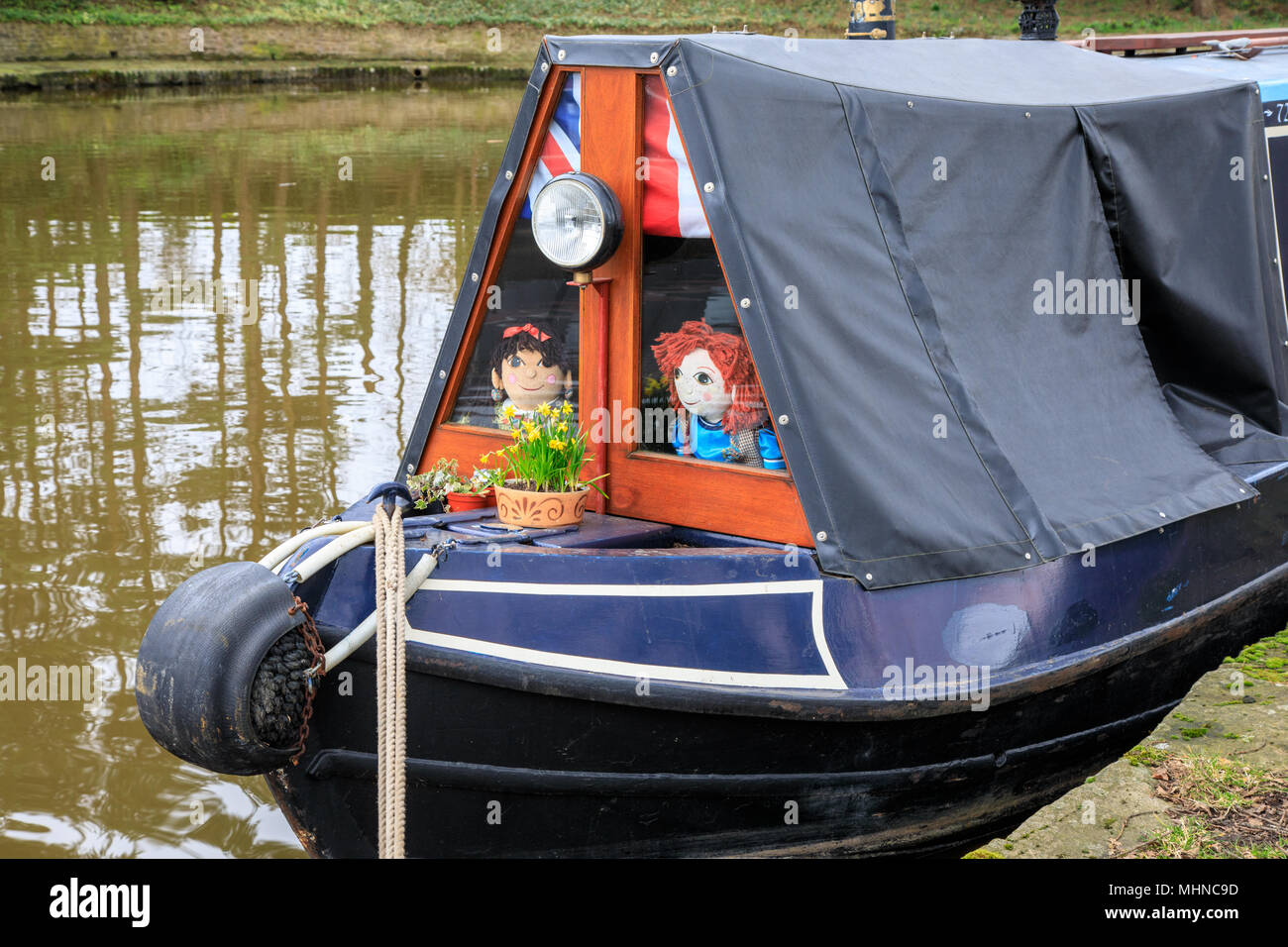 Old fashioned canal narrowboat with a canvas cover.  On the Macclesfield canal the narrow boat has a tarpaulin covered roof.  Toys are in the windows Stock Photo