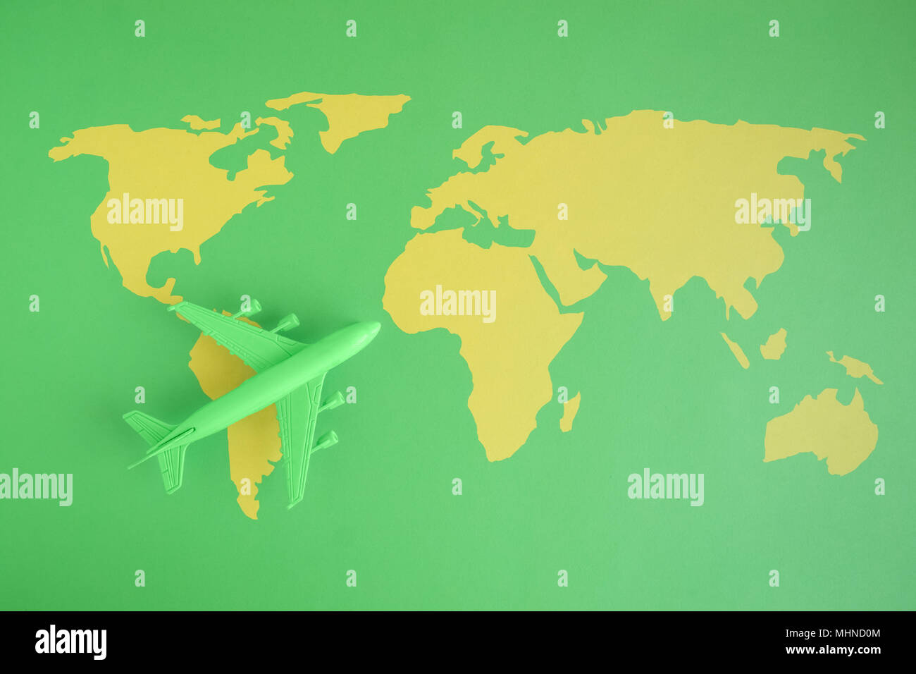 Simple flat map of world with countries stock photos simple flat flat lay of miniature toy airplane on green background with world map minimal trip and travel gumiabroncs Image collections