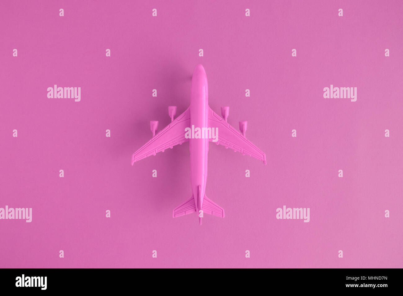 Flat lay of miniature toy airplane on pink background minimal trip and travel creative concepts. Stock Photo